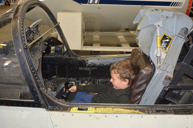 Calvin in a jet trainer cockpit on USS Midway