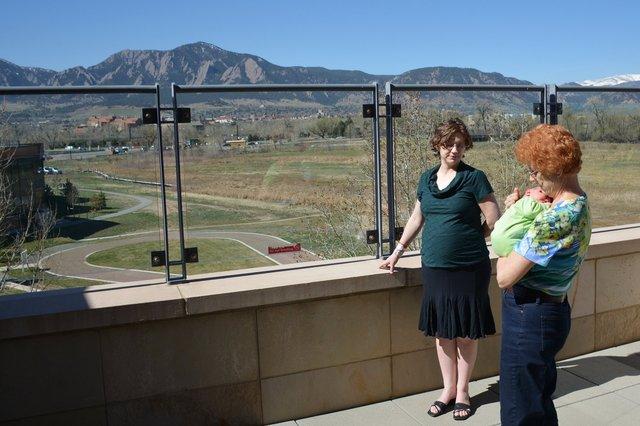 Kiesa, Grandma, and Julian on the balcony with a view of the Flatirons