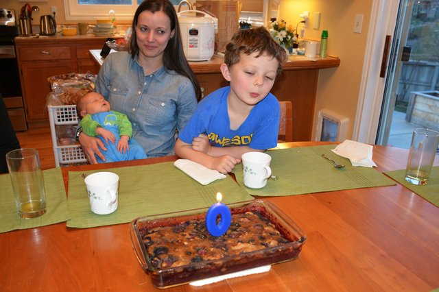 Calvin blows out Julian's zeroth birthday cake while Aunt Bethany holds Julian
