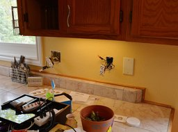 Electrical rewiring in process on kitchen counter