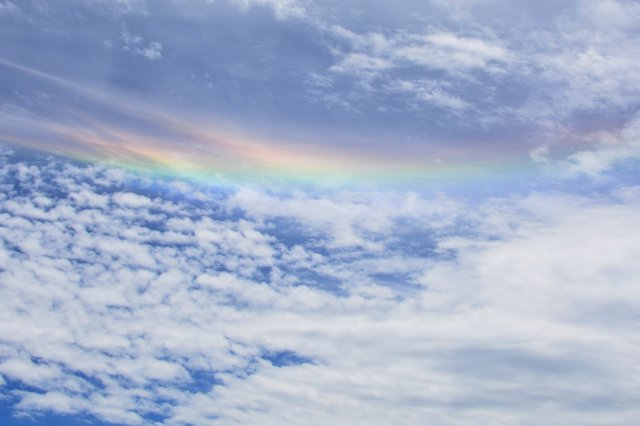 Interstitial rainbow in middle of cloud