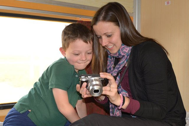 Calvin reviews photos with Aunt Bethany on the train to Jaipur