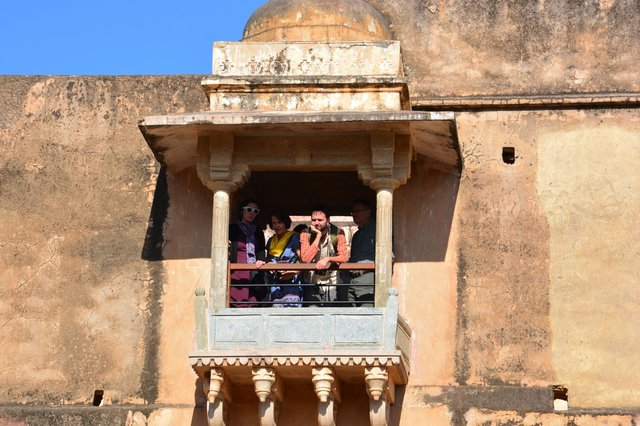 Bethany, Mom, Willy, and Dad look through a window at Amber Fort