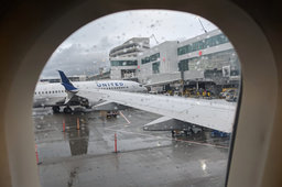 Looking out the window onto a rainy tarmac at SEA