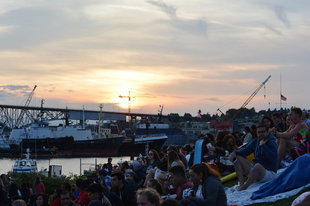 Sun sets over the Aurora Bridge while people wait for fireworks at Gasworks Park