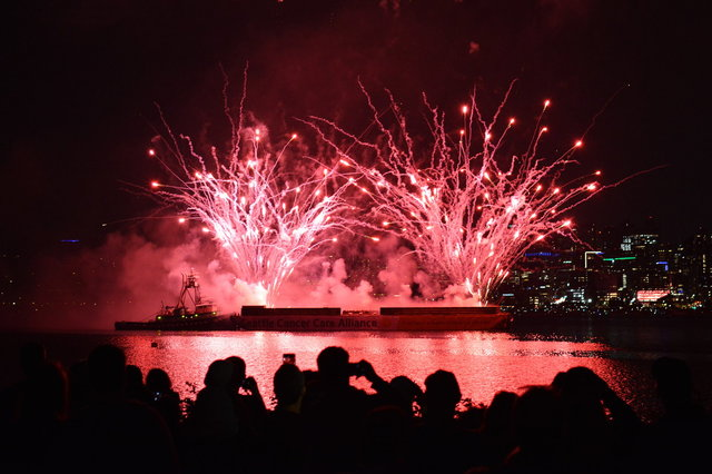 People watch fireworks erupting from the barge in Lake Union
