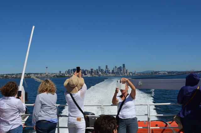 Passengers watch the Victoria Clipper V leave Seattle