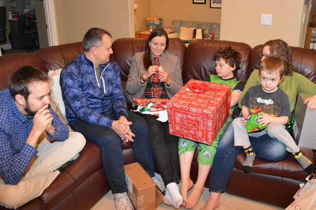 Bethany opens Christmas presents, with Willy, Josh, Calvin, Kiesa, and Julian