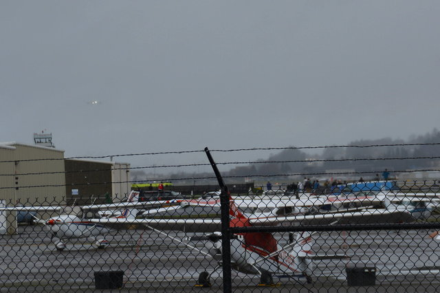 777X first flight N779XW approaches Boeing Field through the clouds