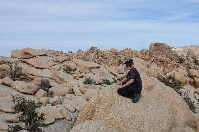 Calvin sits on a boulder overlooking Hidden Valley