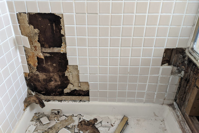 Tile removed, exposing rotten drywall