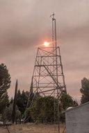 Sun sets through wildfire haze above radar tower