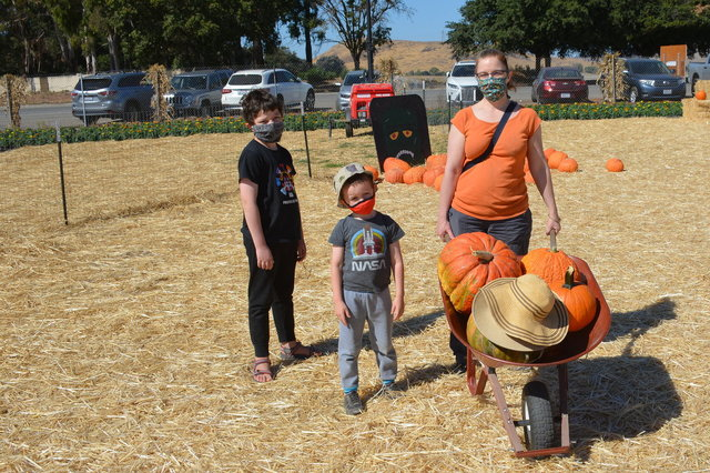 Calvin, Julian, and Kiesa carry pumpkins in a wheelbarrow