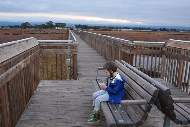 Julian eats a snack at the end of the boardwalk at Baylands