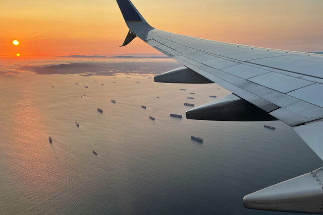 737 wing flying over the Port of Long Beach at sunset
