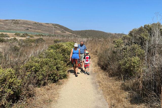 Nana, Grandpa, and Julian walk to the beach