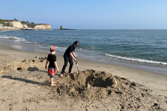 Julian watches Calvin expand his foxhole on Four Mile Beach