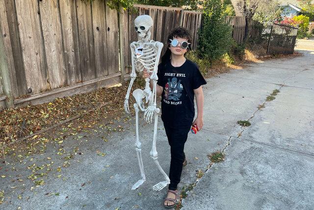 Calvin carries a plastic skeleton