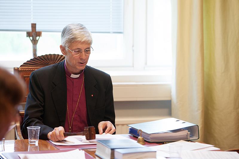 Piispa istuu kokouspöydän päässä kädessään puheenjohtajan nuija.
