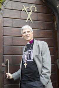 Hymyilevä piispa Repo piispantalon ulko-ovella, käsi ovenkahvalla.