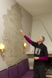 Piispa Repo piispantalon aulassa, vanhaa hiippakuntaa esittävän seinämaalauksen edessä, osoittaa kädellään seinämaalauksen marttaa.