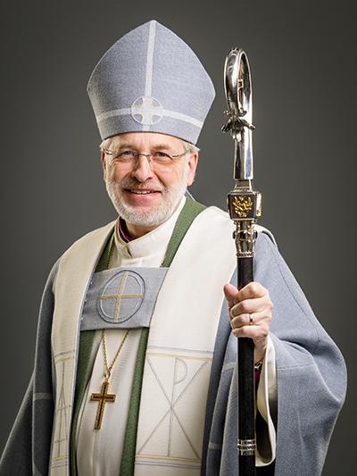 Piispa Simo Peura yllään harmaa juhlakaapu