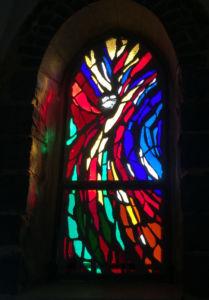 Lasimaalausikkuna pimeässä kirkossa. Kuva-aihe on lähes abstrakti, mutta siinä voi erottaa risriinnaulitun Kristuksen hahmon.