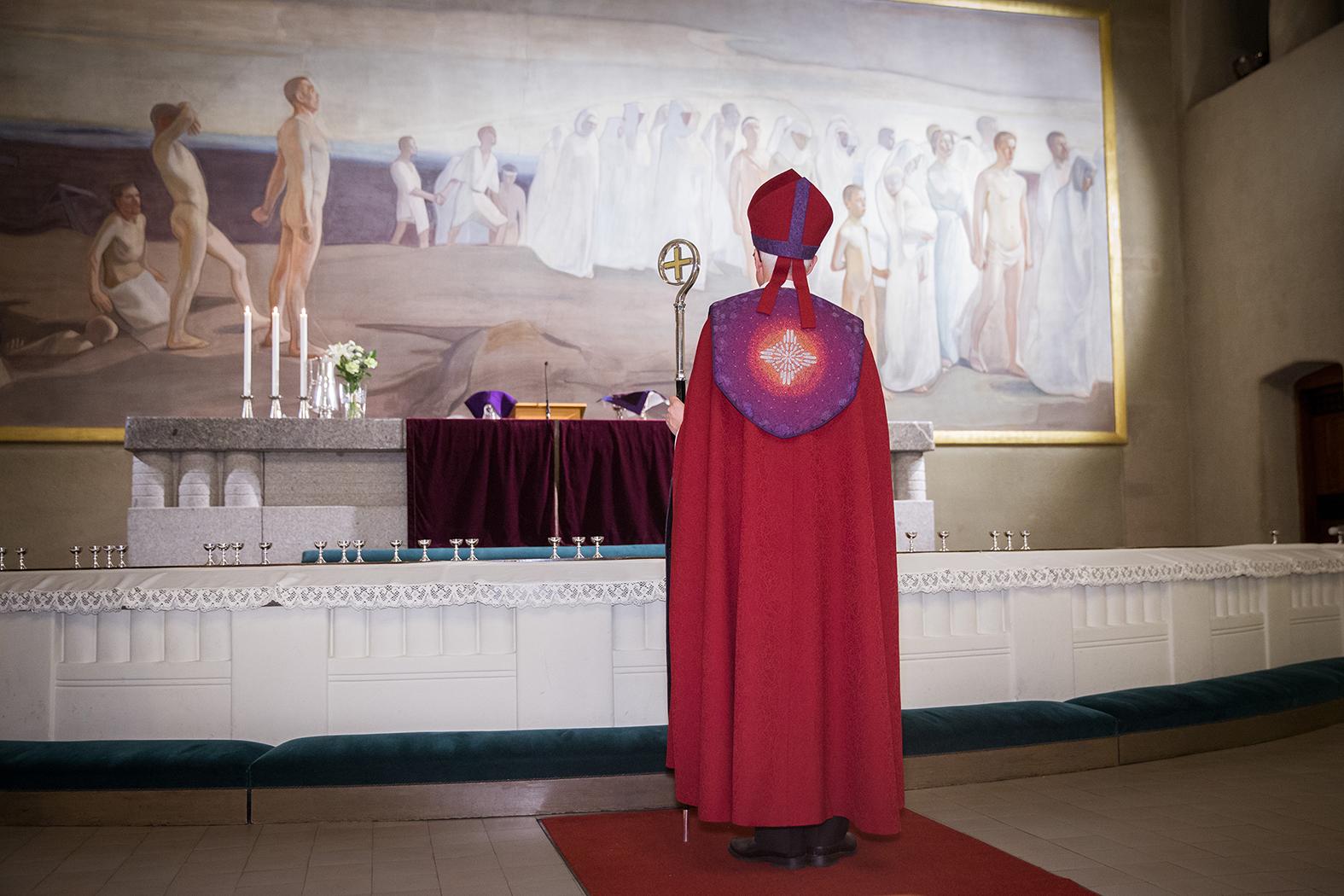 Piispa seisoo Tampereen tuomiokirkon alttaria kohti kääntyneenä yllään punasävyinen piispankaapu ja hiippa.
