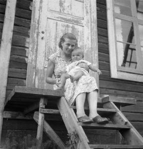 Piispa Kalliala vuonna 1953 vauvana äitinsä sylissä. Äiti istuu puurappusilla