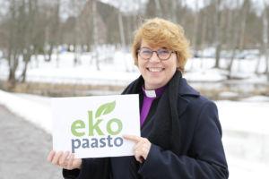 Piispa Kaisamari Hintikka Espoonjoen rannalla kädessään ekopaaston kyltti.