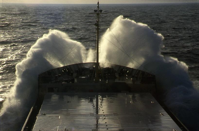 Musta Outokumpulaivan keula ja tummaa vettä vasten suuria vaahtomaisia aaltoja.