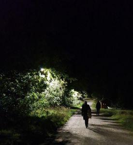 Kävelijöitä pimeässä katulampun valossal