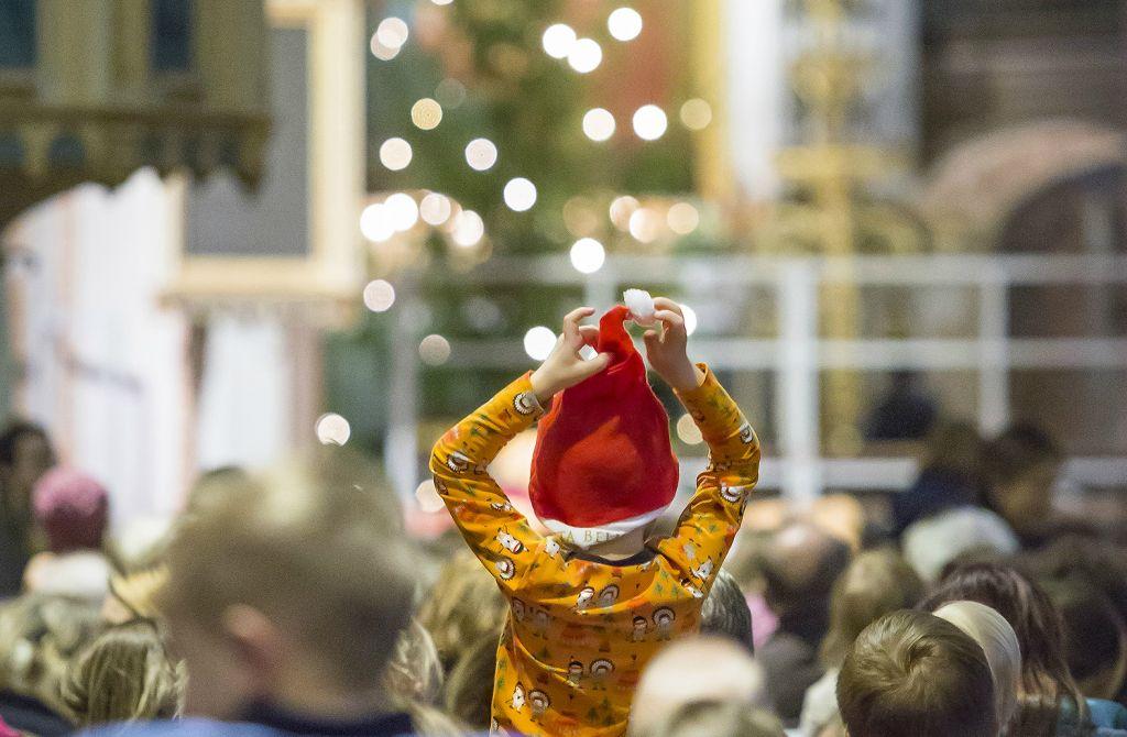lapsi tonttulakissa joulukirkossa