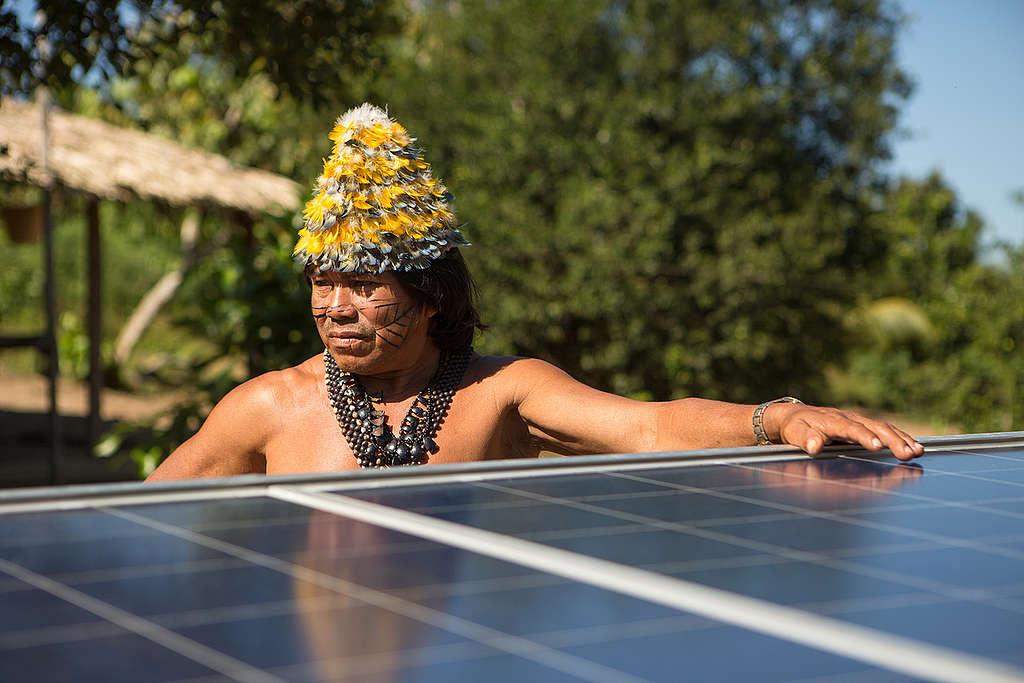 Cacique Munduruku ao lado de placa de energia solar.