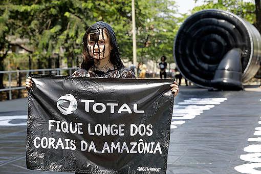 Ativista mulher do Greenpeace segura pintada com petróleo falso segura banner em protesto contra a petrolífera Total.