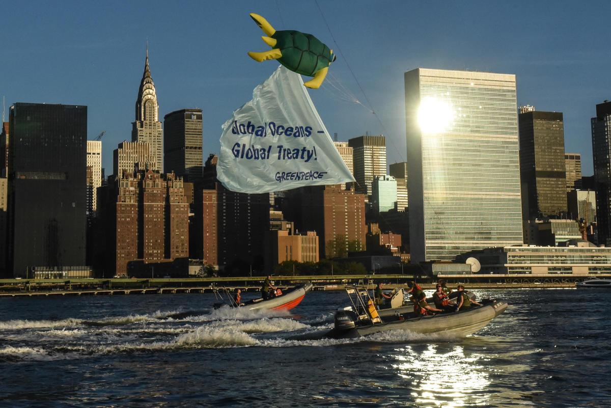 Em bote, ativistas levam uma pipa em formato de tartatuga-marinha para a frente da sede da ONU