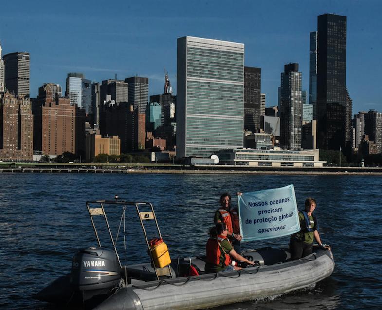 """Ativistas seguram banner com a frase """"Nossos oceanos precisam de proteção global""""."""