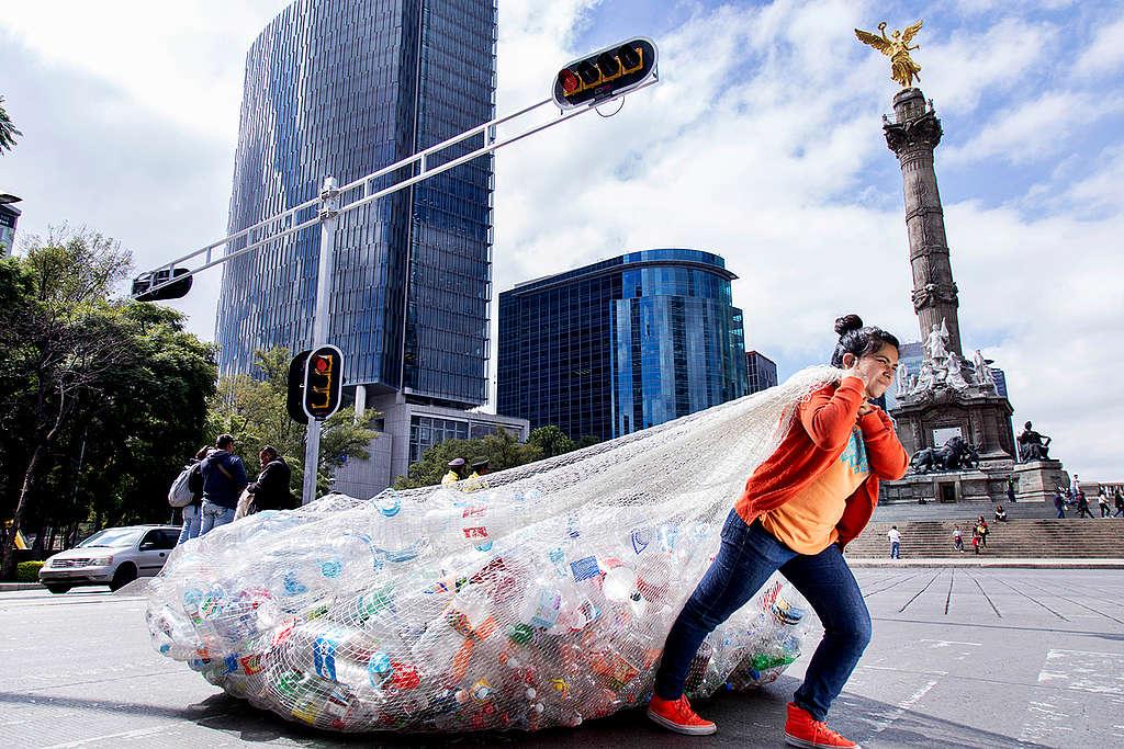 Mulher carrega sacola com lixo plástico.
