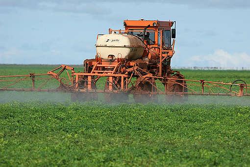 Trator pulveriza agrotóxicos em plantação de soja no Brasil
