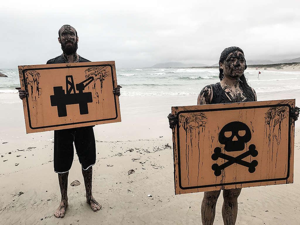 Voluntários do Greenpeace seguram placas com imagem de uma plataforma de petróleo e da morte para protestar contra exploração de petróleo perto dos Corais da Amazônia.