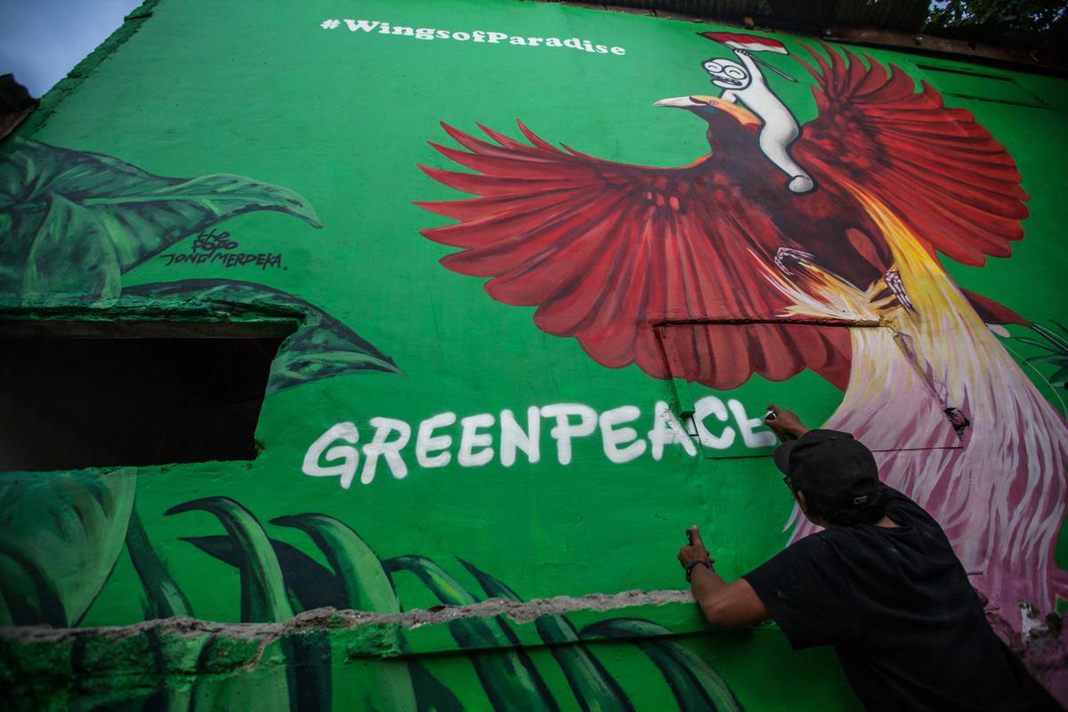 Artista de rua pinta o nome do Greenpeace em mural com aves do paraíso na Indonésia.