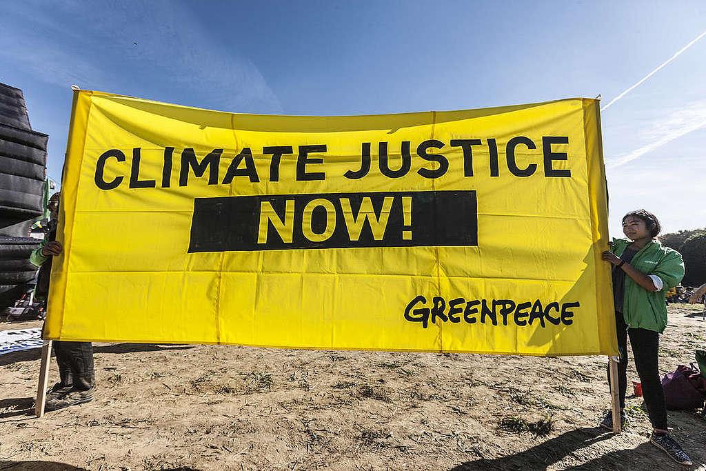Manifestantes seguram placa que diz: 'Justiça para o clima agora!'