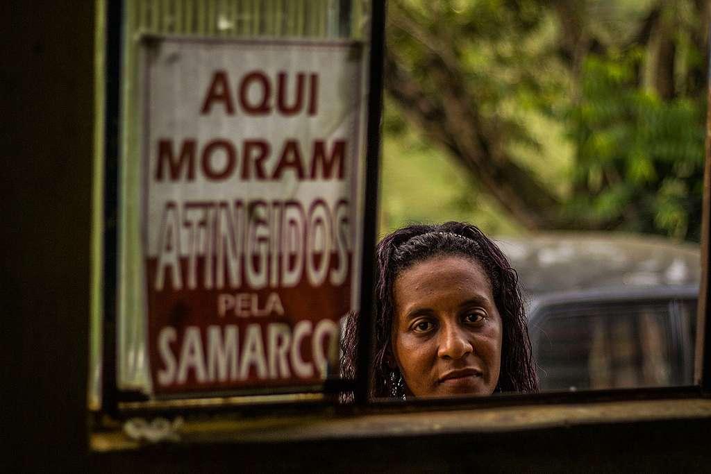 Simone Silva ao lado de placa que diz
