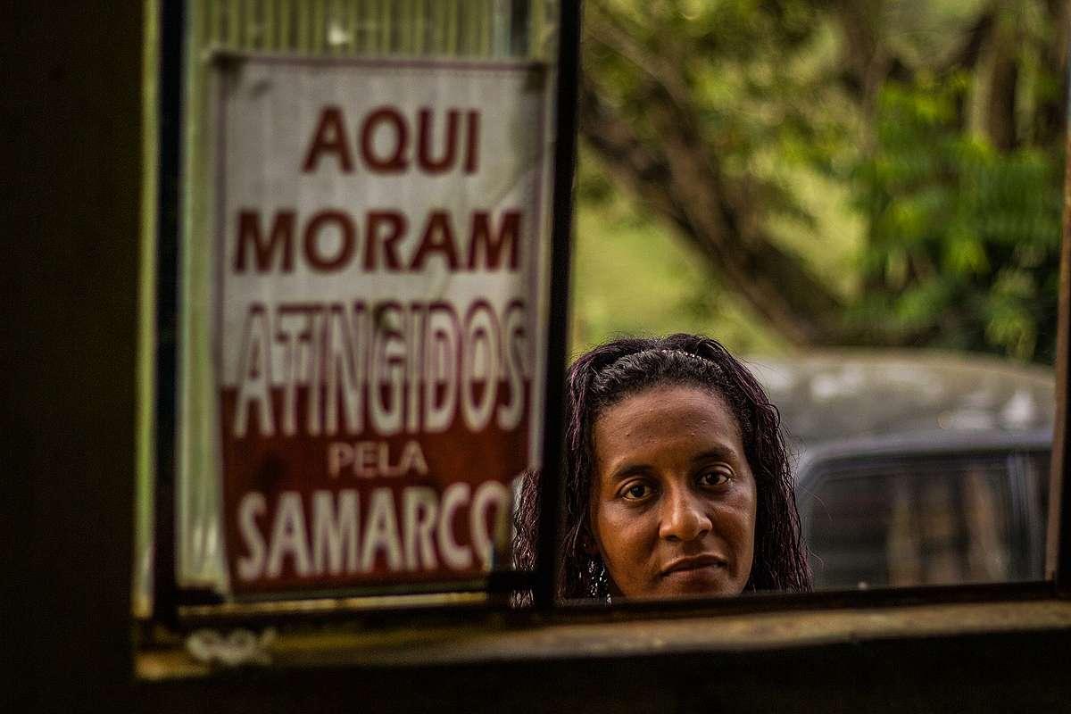 """Simone Silva ao lado de placa que diz """"Aqui moram atingidos pela Samarco"""""""