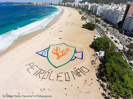 """Frase """"petróleo não"""" formada na praia por 500 pessoas. Em cima, o desenho de um peixe formado por tecidos"""