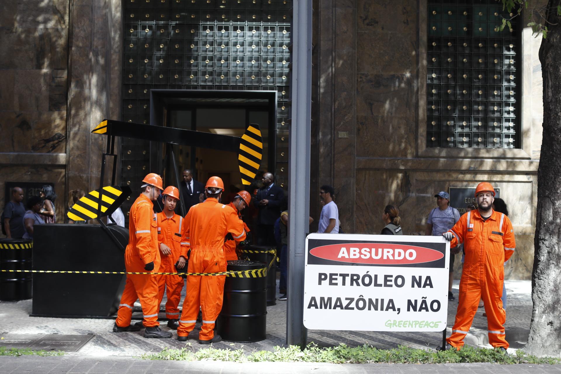 pessoas simulam a exploração de petróleo com uma máquina e barris em frente ao prédio do governo.