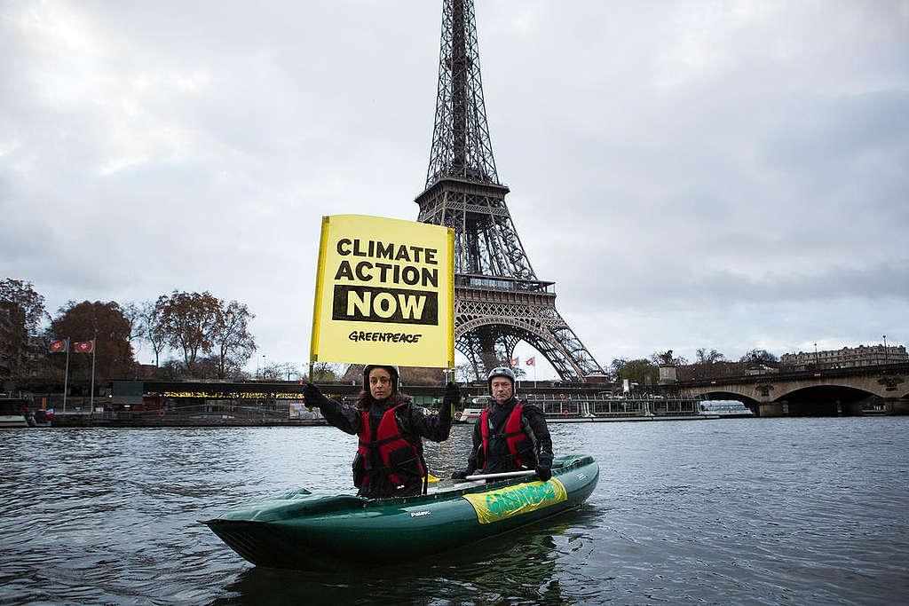 Ativista em caiaque segura um banner pedindo mais ação climática, em frente à torre Eiffel. © Jean Nicholas Guillo
