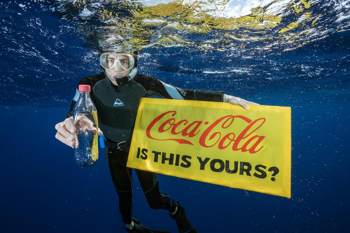 Mergulhador com garrafa plástica, segura um banner com a inscrição: Coca-Cola, isso é de vocês? © Justin Hofman