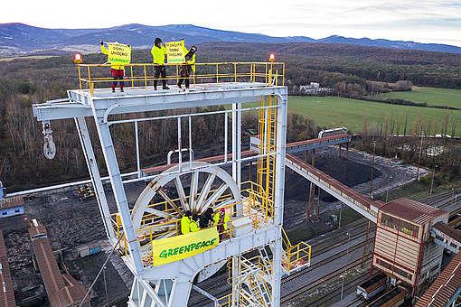 Ativistas do Greenpeace seguram um banner em uma torre de uma mineradora