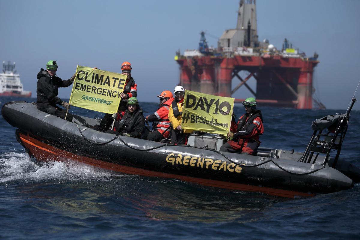 """Ativistas a bordo de bote inflável com cartazes contendo """"Emergência Climática"""". © Greenpeace"""
